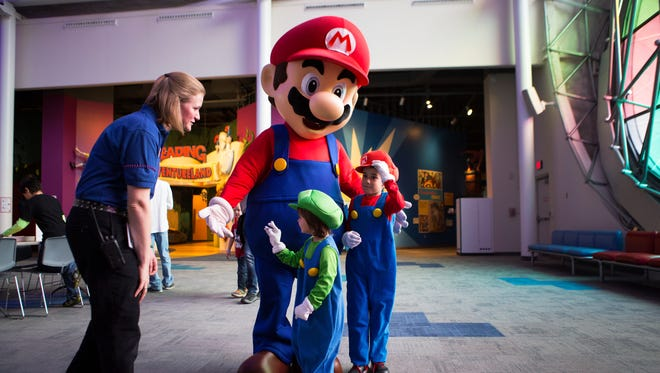 Caitlin and Aidan Thireos of Penfield wear their Mario and Luigi halloween costumes as they meet Mario at the Playing with Power: 30 Years of the Nintendo Entertainment System exhibit opening at the Strong Museum of Play on Saturday, October 24, 2015.