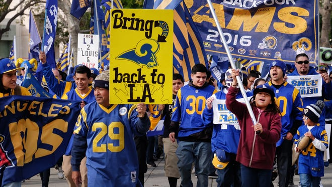 Rams football fans hold banners, wave signs and chant while marching around the historic Los Angeles Memorial Coliseum. Saturday, Jan. 9, 2016 in Los Angeles. Boisterous Los Angeles Rams fans gathered Saturday to herald the NFL football team's possibly imminent return to Southern California after a 21-year sojourn in St. Louis. (AP Photo/Richard Vogel) ORG XMIT: LA101
