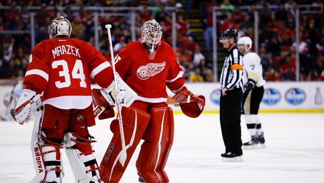 Mar 26, 2016; Detroit, MI, USA; Detroit Red Wings goalie Jimmy Howard (35) skates past goalie Petr Mrazek (34) to replace him in the second period against the Pittsburgh Penguins at Joe Louis Arena.