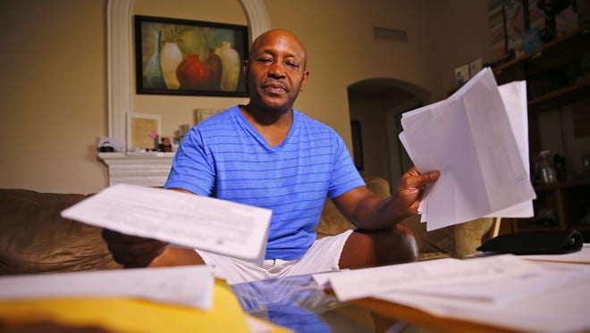 William Wright sorts through legal papers at his home on Monday, Aug. 29, 2016, in Mesa. Wright was fired from his correctional officer job at Phoenix's Adobe Mountain School in July when he was unable to return to work after suffering injuries on the job.