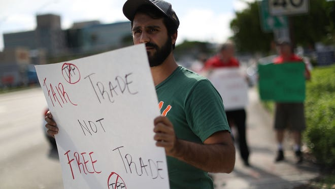 Farbod Tehranian joins with other protesters from the Labor Council of Latin American Advancement (LCLAA) , CWA and other South Florida unions, Citizens Trade Campaign and community activists to ask that the Florida members of the U.S. Congress oppose the Trans-Pacific Partnership (TPP) trade deal on September 14, 2016 in Doral, Florida. The protesters feel that the TPP would ship jobs overseas to low-wage countries and erode health, safety and environmental protections.  (Photo by Joe Raedle/Getty Images)