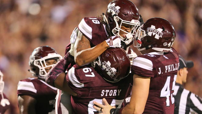 Mississippi State's Deddrick Thomas (18) celebrates with teammates after scoring a touchdown.