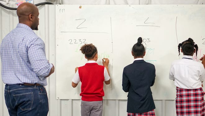 An instructor at T.M. Landry College Prep watches as students work on a lesson.