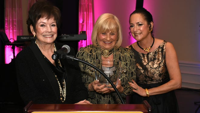 Special honoree Jackie Pierce, center, receives a butterfly bowl from former president Rosemary Wick and Hyla Crane. The Marco Island Center for the Arts held their annual gala Saturday evening at Island Country Club.