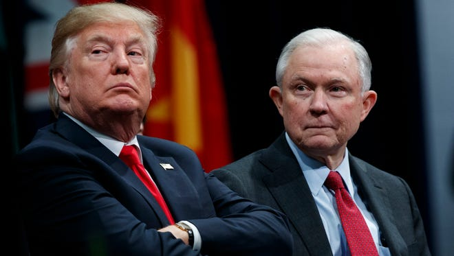 In this Dec. 15, 2017 file photo, President Donald Trump, left, sits with Attorney General Jeff Sessions during the FBI National Academy graduation ceremony in Quantico, Virginia. (AP Photo/Evan Vucci)