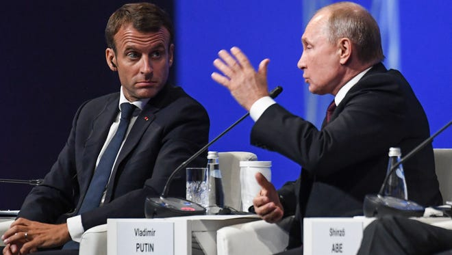 Russian President Vladimir Putin and French President Emmanuel Macron attend a session of the St. Petersburg International Economic Forum on May 25, 2018 in St. Petersburg.