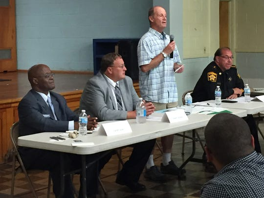 Steve O'Connell (standing) moderates a July 10 public forum for Milwaukee County Sheriff candidates Earnell Lucas (left), Deputy Robert Ostrowski (second from left) and Acting Sheriff Richard Schmidt (right). The Sherman Park Community Association sponsored the forum at Albright United Methodist Church.