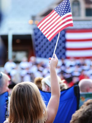 """In this file photo, Missy Bisher waves an American flag while the Lafayette Citizens Band and the Freedom Singers perform """"America, the Beautiful"""" during the Stars and Stripes Celebration, July 4, 2012."""
