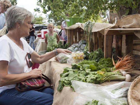 Pat Norton from Enterprise buys vegetables during the Wednesday farmers market in Cedar City last year.