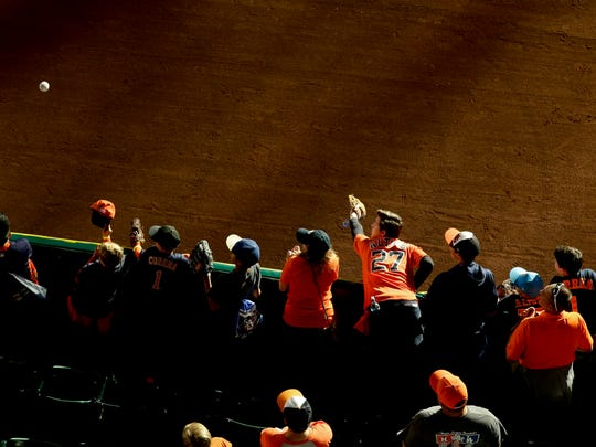 Fans try for a fly ball during batting practice before Game 5 of baseball's World Series between the Los Angeles Dodgers and the Houston Astros Sunday, Oct. 29, 2017, in Houston. (AP Photo/Charlie Riedel)
