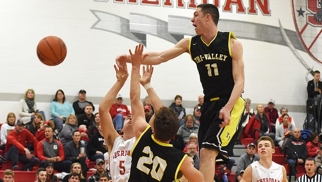 Tri-Valley's Jake McLoughlin blocks a shot by Sheridan's Noah Cooperrider during the Scotties' 63-61 win earlier this season at Glen Hursey Gymnasium. McLoughlin's interior presence has helped key the team's Muskingum Valley League title chances.