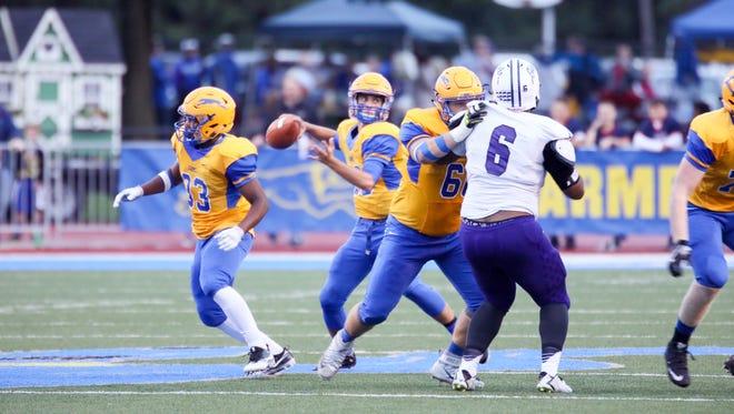 Carmel's quarterback Jake McDonald drops back to pass against Ben Davis on Friday night. The Greyhounds won 40-36.