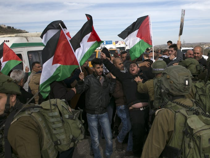 Palestinian demonstrators raise their national flags