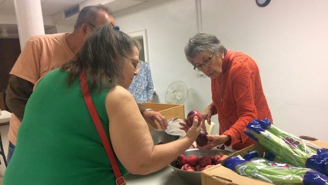 Volunteer worker Donna Jansen, right, helps clients pick apples and other fresh produce at the Presbyterian Food Pantry of Green Bay at First Presbyterian Church in Green Bay on Tuesday, Oct. 11, 2016.