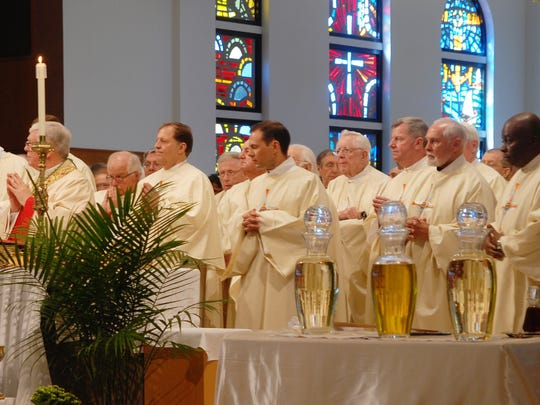 Rev. James Simko of Naples prays behind the bishop at a mass earlier this week. Simko has been a priest for 25 years.