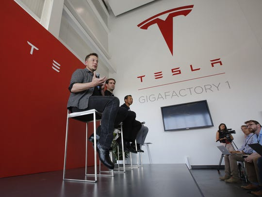 In this July 26, 2016, file photo, Elon Musk, CEO of Tesla Motors Inc., left, discusses the company's new Gigafactory in Sparks, Nev.