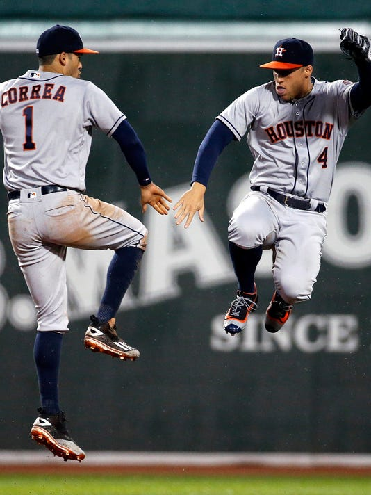 Houston Astros' Carlos Correa (1) and George Springer (4) celebrate after the Astros defeated the Boston Red Sox 7-6 during a baseball game in Boston, Friday, May 13, 2016. (AP Photo/Michael Dwyer)