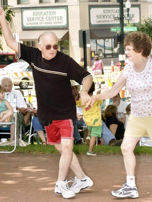 Jack and Ginny Boerstler, of Lancaster, dance to the music of Brass Taxi during a lunch concert at the Lancaster Festival on Zane Square in Lancaster July 18, 2003.