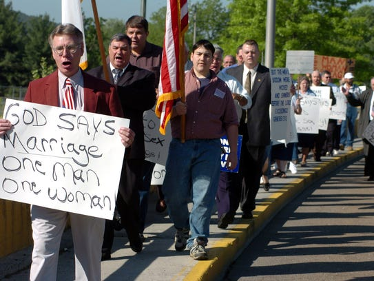 Rev. Franklin Raddish, front, leads protest against