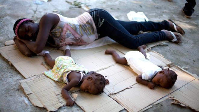 Marie Matte Mayan 26, sleeps on the floor with her twins, Maudeline and Maudena Pierre an a shelter after being deported by Dominican Republic authorities, in Croix-des-Bouquets, Haiti on Sunday.