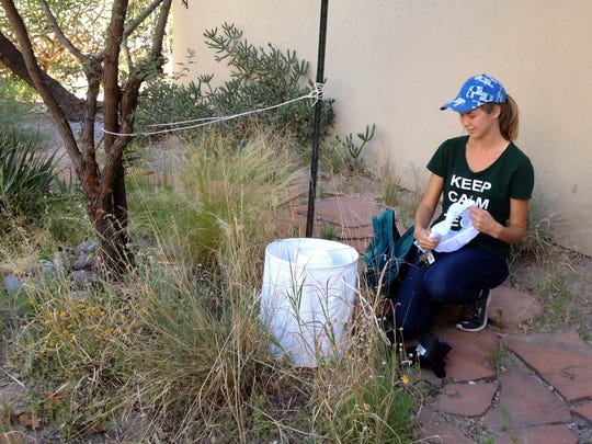 NMSU graduate student Stephanie Mundis demonstrates how to set up one of the mosquito traps she will be using this summer as she travels around the state to capture mosquitoes and examine them and their environment to create a map of mosquito populations across New Mexico.