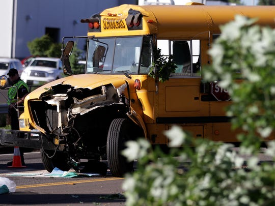 Emergency personnel clean up the scene after a school bus collided with several trees and a retaining wall on Salem Parkway near Cherry Avenue in Salem on Tuesday, June 9, 2015. No students were on board and the driver was not injured.