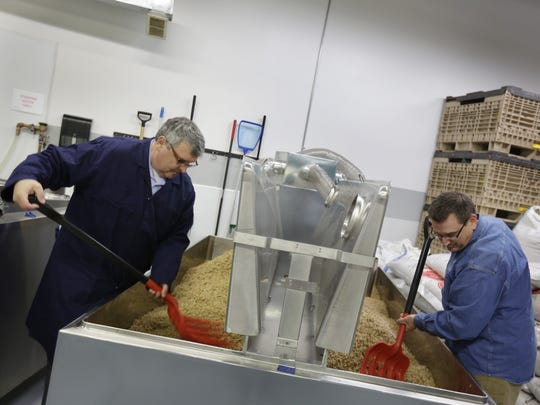 Tom Laboda, right and Dan Bailey founders of MotorCity MaltHouse turn the malt in a tank at their facilities in Shelby Township on Monday, Dec. 21, 2015.