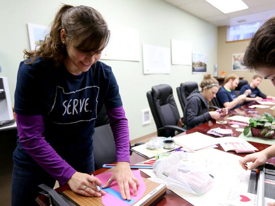 Emma Felzien, an adjunct professor of chemistry, left, and other Corban University students and staff volunteer to make Valentine's Day decorations as part of a Martin Luther King Jr. Day service project at the Union Gospel Mission in downtown Salem on Monday, Jan. 18, 2016.