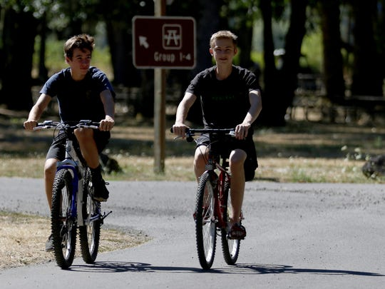 Cousins Zach Juenger, left, 16, of Vancouver, Wash., and Brayden Spencer, 16, of Springfield, Ore., ride their bikes at Champoeg State Heritage Area on Tuesday, Aug. 16, 2016.