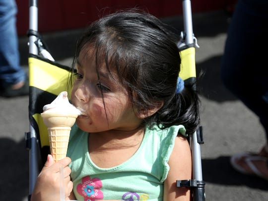 Estrella Gonzalez, 3, of Salem, licks an ice cream cone on the first day of the Oregon State Fair in Salem on Friday, Aug. 26, 2016. Temperatures reached 98 degrees on Friday.
