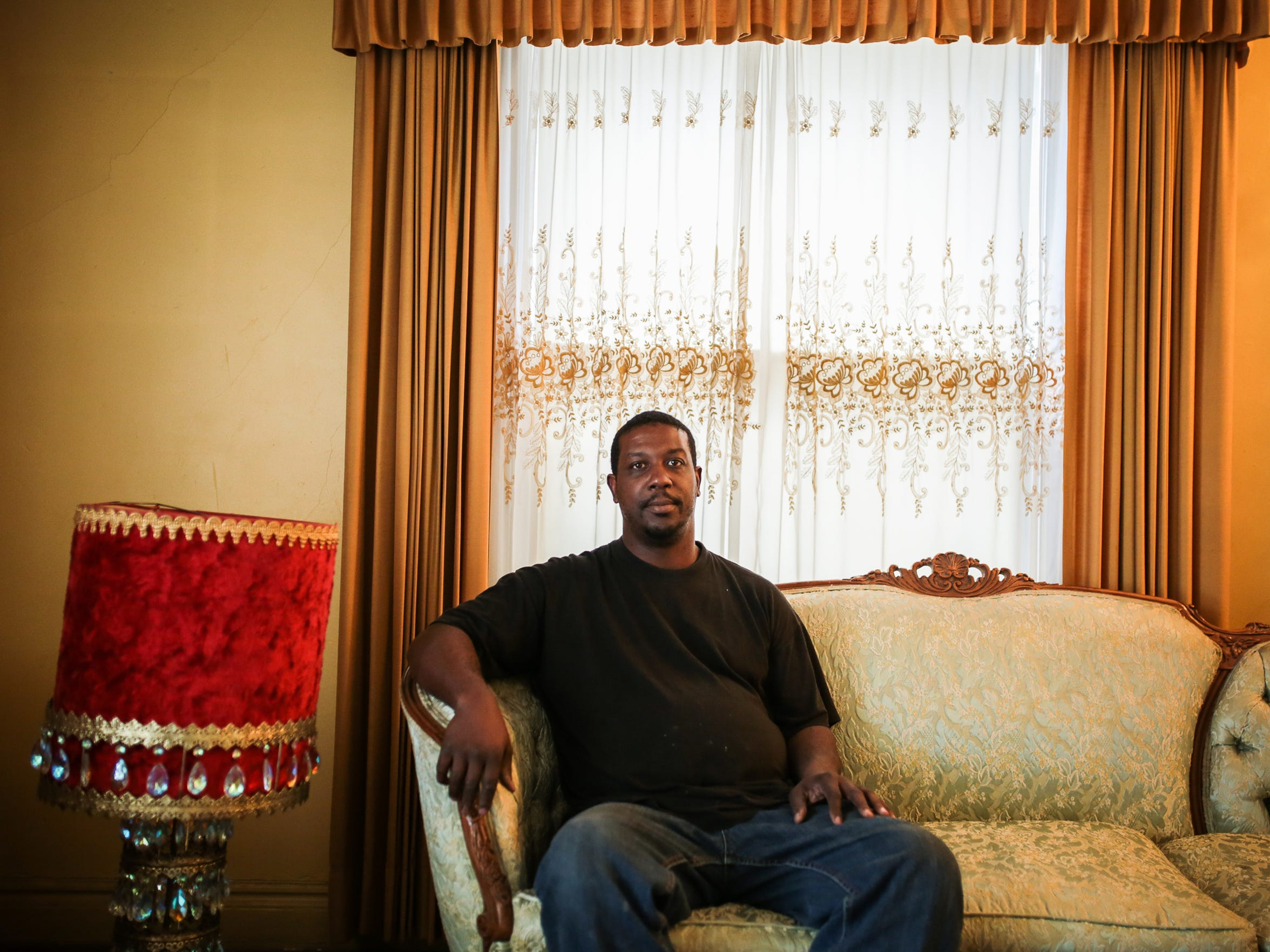 "Alonzo Green, 44, of Detroit, sits on his mother's old couch in the living room of her former home on March 8, 2017, on Bewick Street on Detroit's east side. ""After my dad passed I came back to rekindle with my brothers and be close to my mom, whenever she does pass I didn't want to be too far, and I missed home. This is really my home."""