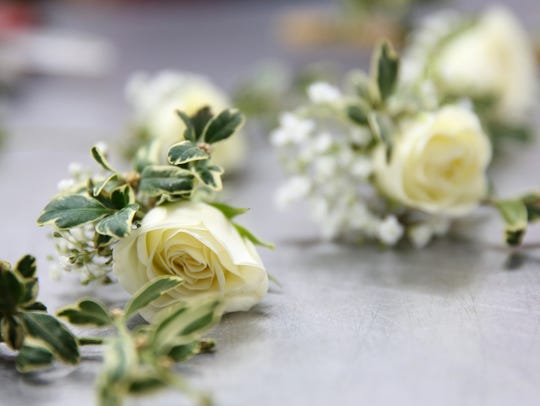 White roses are cut before being added to a corsage