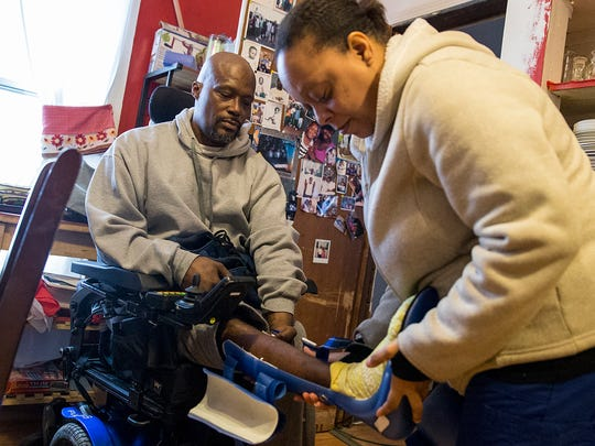 Physical therapist Belinda Smith helps Gerald Cole with his leg braces so they can do daily therapy at his near east side home, Wednesday, Feb. 21, 2018. Smith works in-home with Cole, who is paralyzed from the waist-down, on rehabilitation five days a week. He was shot and paralyzed by IMPD officer James Perry in October 2016.