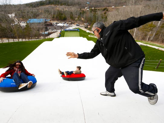 Wolfe Mountain employee Jason Johnson gives Pierce Adams' tube a spin as he begins his trip down the new Snowflex tubing hill at Wolfe Mountain on Friday, Dec. 1, 2017.