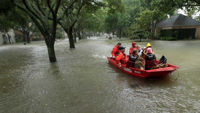 A Coast Guard rescue team evacuates people from a neighborhood inundated by floodwaters from Tropical Storm Harvey on Monday in Houston.