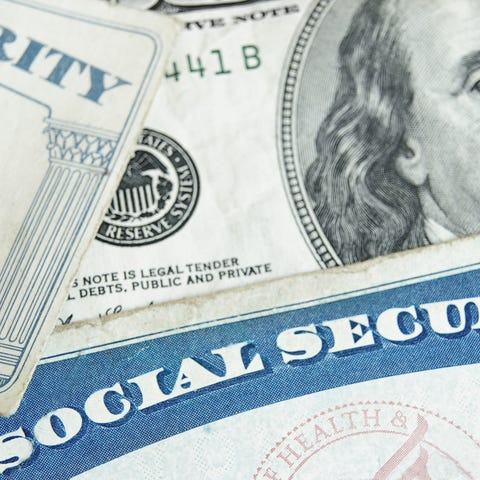 Two Social Security cards partially covering a...