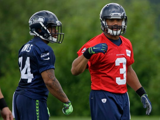 Thomas Rawls, left, works with Russell Wilson during