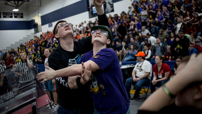 RoboSapiens 4779 member Dominic Jakubowski reacts and hugs Mecanum Knights 3667 member Josh Stover as they look up at the scoreboard to see that their alliance won during a FIRST Robotics District Event at Marysville High School.
