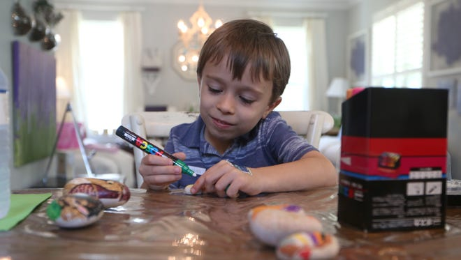 Trace Dalton, 5, paints a rock at a painting party hosted at the home of artist Karen Robertson, creating both 'Tallahassee Rocks' themed designs and kits for donation so others can create their own designs.