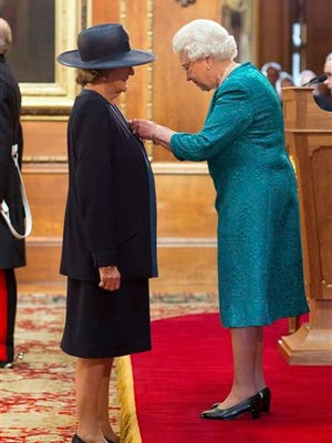 Dame Maggie Smith is made a member of the Order of the Companion of Honour by Queen Elizabeth II during an investiture ceremony at Windsor Castle, England, Friday.