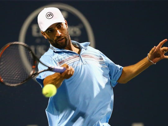 James Blake returns a forehand to Andy Roddick during