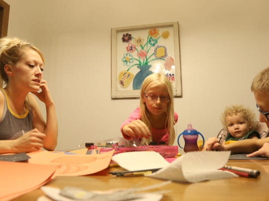 Keira Tellekson, 10, reaches for a different color crayon to draw with at the Tellekson residence in Wisconsin Rapids, Wisconsin. Karly Tellekson was bullied as a child, and was cautious in talking to adult figures, even blamed herself for it. Now, she learns from her own experiences when talking to her children.