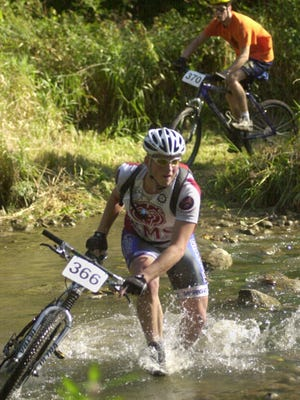 Racers splash across Mill Creek during a mountain bike race.