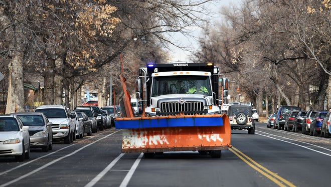 A plow heads south on Remington Street applying salt brine on Tuesday, December 6, 2016.