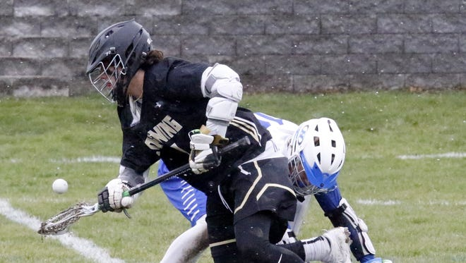 Corning's Collin Neally breaks through after winning a faceoff against Kaelan Winkky of Horseheads on Friday during boys lacrosse action at Horseheads High School.