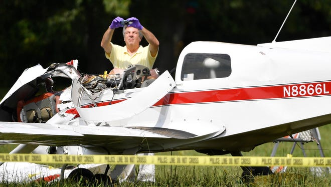 An FAA investigator takes photos at the scene of a plane crash in Portland Wednesday, Aug. 30, 2017. According to a spokesperson for the FAA,  the Grumman American AA-1B was approaching the Portland Municipal Airport Tuesday night, Aug. 29, when it crashed roughly 2,500 feet from the end of Runway 1.