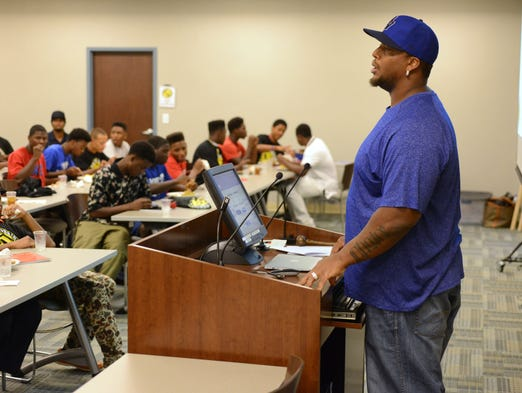 Former NFL defensive tackle Fred Robbins talks area high School football players and parents Wednesday during Mr. Robbins Neighborhood football camp at EXOS formerly Athletes Performance in Gulf Breeze.
