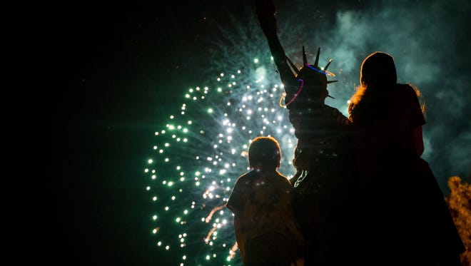 Children stand on the Statue of Liberty in City Park to watch the Fourth of July fireworks on July 4, 2016.