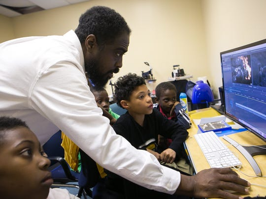 Multimedia instructor Hashim Yasin shows kids how to use a movie editing software at Reeds Refuge in Wilmington.