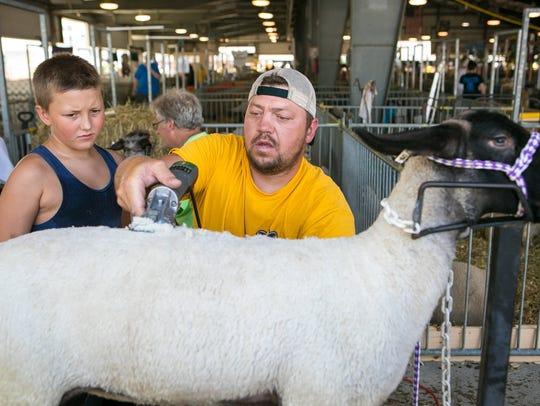 Travis Allaband of Camden shows his son Caden, 9, how